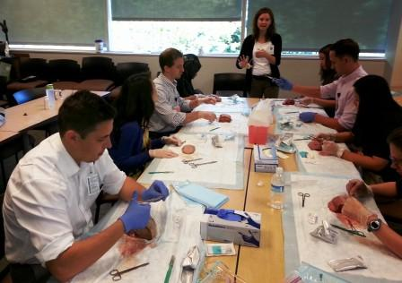 VFM faculty, Dr. Rudisill, teaching suturing techniques using cow tongues for practice