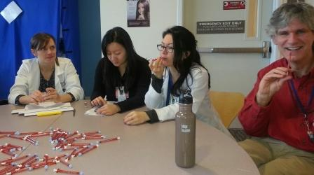 VFM Faculty, Dr. Drew Fillipo (far right) teaching interns about pediatric meds. Interns, L to R: Kate Uvelli, Angela Zhang, Leanne Jones